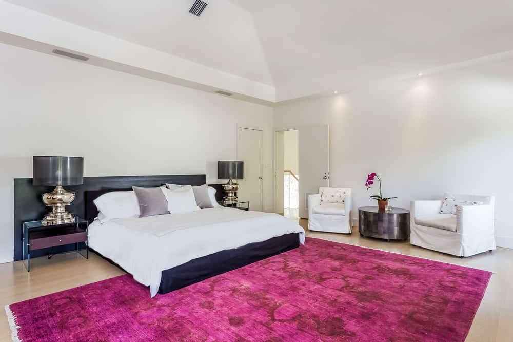 This spacious and bright bedroom is complemented by a large pink area rug that covers most of the light hardwood flooring at the foot of the bed with a contrasting black headboard. Images courtesy of Toptenrealestatedeals.com.
