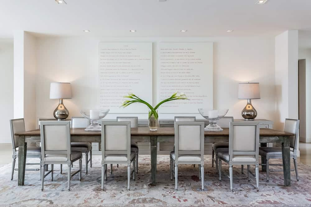 This is a closer look at the dining area beside the living room. It has a large dining table surrounded by chairs with cushioned seats and backs with a bright background adorned by a couple of table lamps. Images courtesy of Toptenrealestatedeals.com.