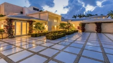 This is the front view of the beautiful house featuring a large courtyard and driveway leading to the attached two-car garage. The main house is glowing warmly with yellow lights coming from the various glass doors and windows of the house. Images courtesy of Toptenrealestatedeals.com.