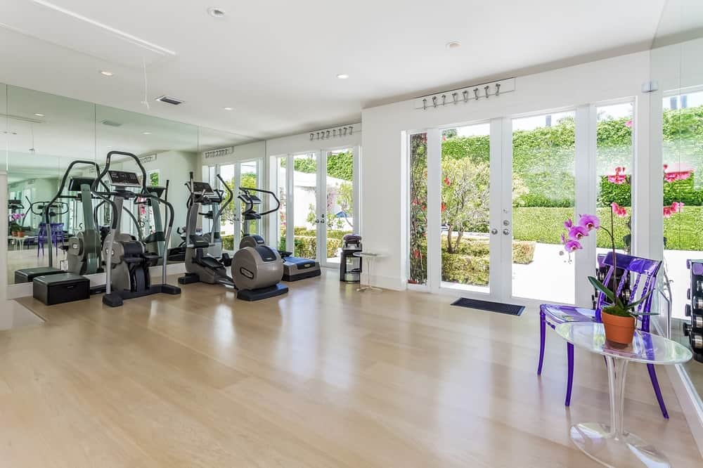 This large area has a fully equipped gym with machines standing out against the white walls, ceiling and light hardwood flooring that are brightened by the large glass doors. Images courtesy of Toptenrealestatedeals.com.