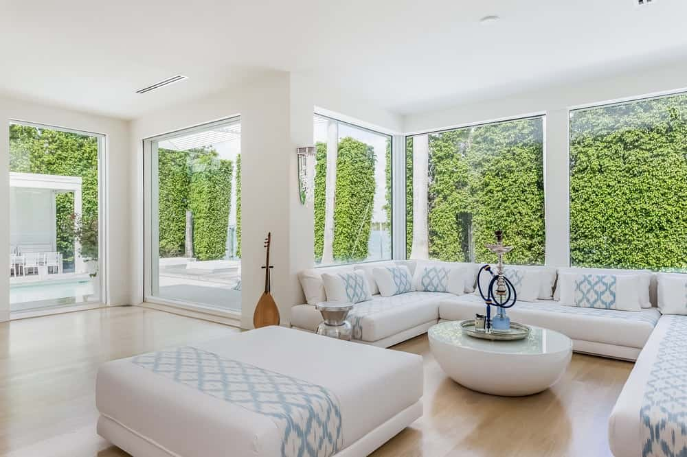 This is the designated hookah lounge of the entertainment wing of the house. It has a white cushioned sectional sofa under the large glass windows paired with a round white coffee table. Images courtesy of Toptenrealestatedeals.com.