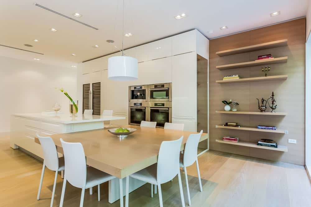 The other edge of the white kitchen island is fitted with a wooden table for an informal dining area paired with white modern chairs. Images courtesy of Toptenrealestatedeals.com.