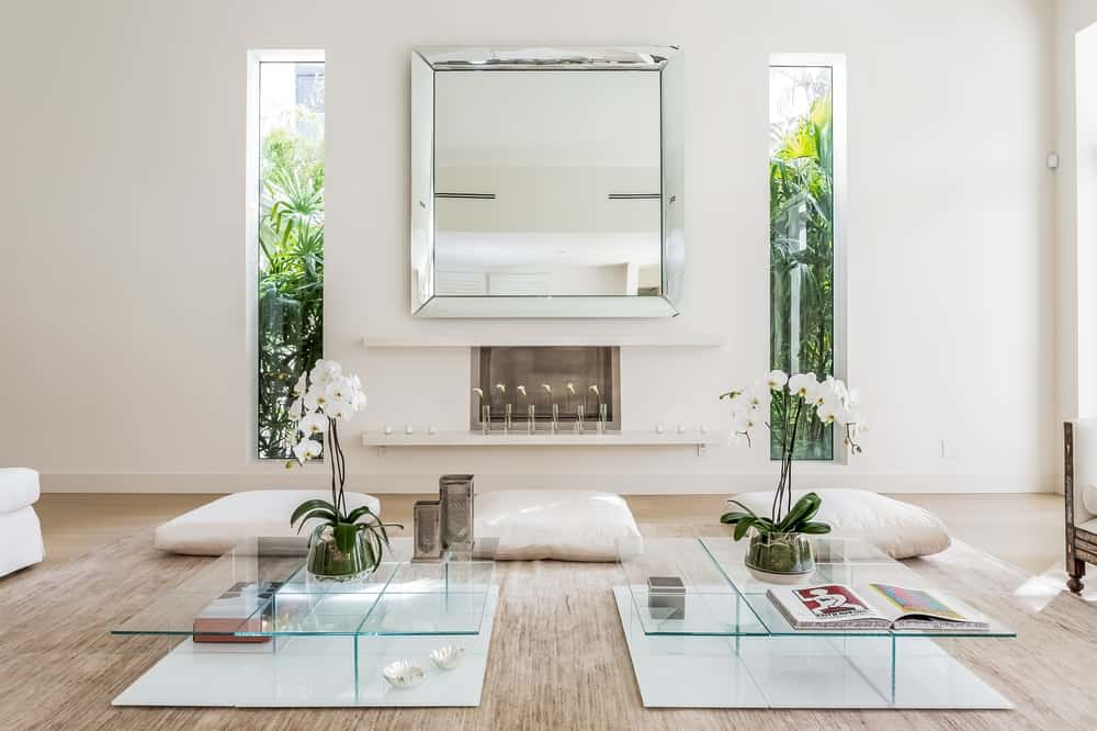 This is the angle of the living room with a focus on the other side of the glass coffee tables that has cushions on the floor next to the modern fireplace topped with a large decorative mirror. Images courtesy of Toptenrealestatedeals.com.