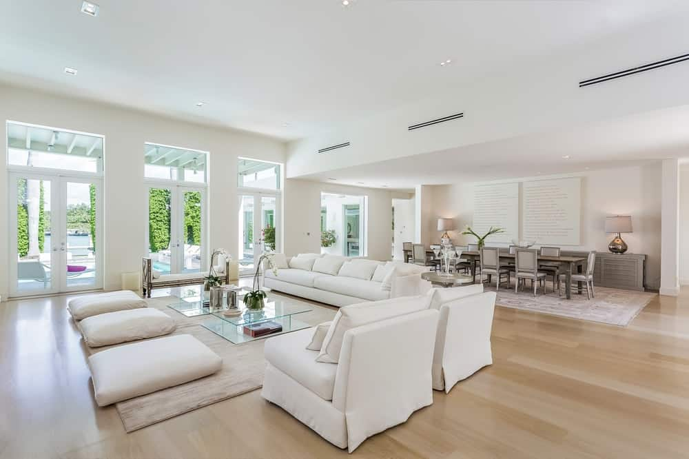 The bright cushioned chairs and sofa of the living room matches well with the bright ceiling and walls illuminated by the tall glass doors. Images courtesy of Toptenrealestatedeals.com.