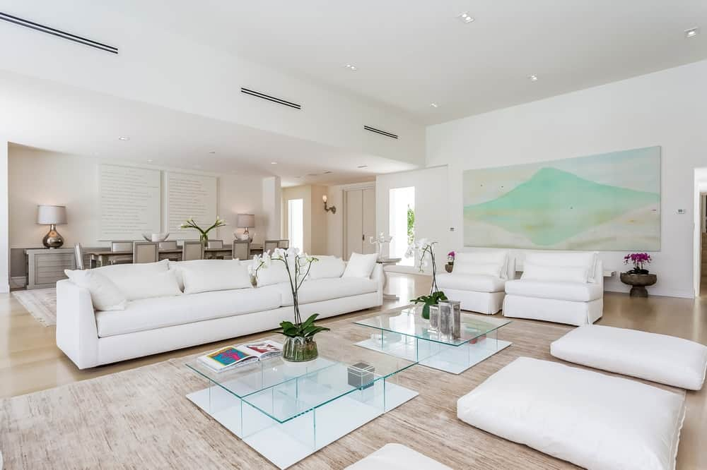 This is a bright and spacious great room that houses the living room with a couple of glass coffee tables in the middle of bright sofas and cushioned chairs. Images courtesy of Toptenrealestatedeals.com.