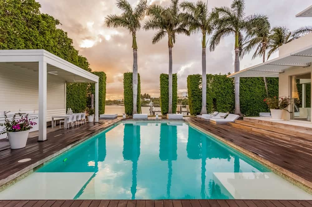 This is a sunset view of the poolside area that highlights the gorgeous tall tropical trees and tall hedges of shrubs that provide additional beauty and privacy. Images courtesy of Toptenrealestatedeals.com.