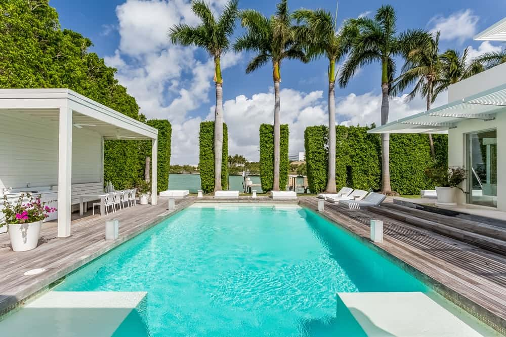 This view of the pool features outdoor areas surrounding the pool including the covered area on the left side with a charming dining area. Images courtesy of Toptenrealestatedeals.com.