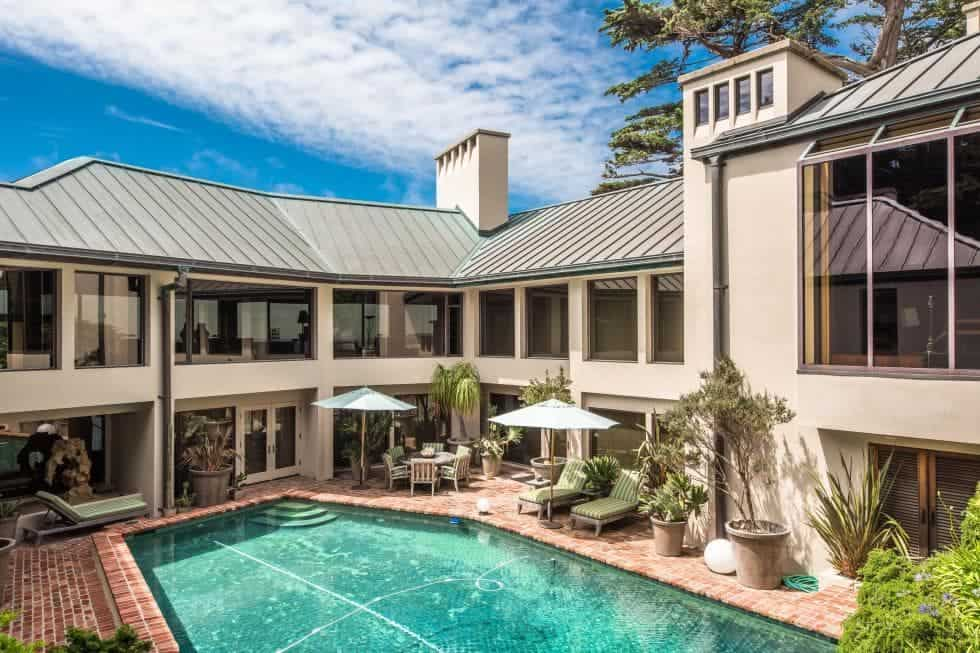 This view of the back of the house shows the immense size of the estate along with the beautiful backyard that has a large pool surrounded by the large glass doors, windows and outdoor areas all centering on the pool. Images courtesy of Toptenrealestatedeals.com.