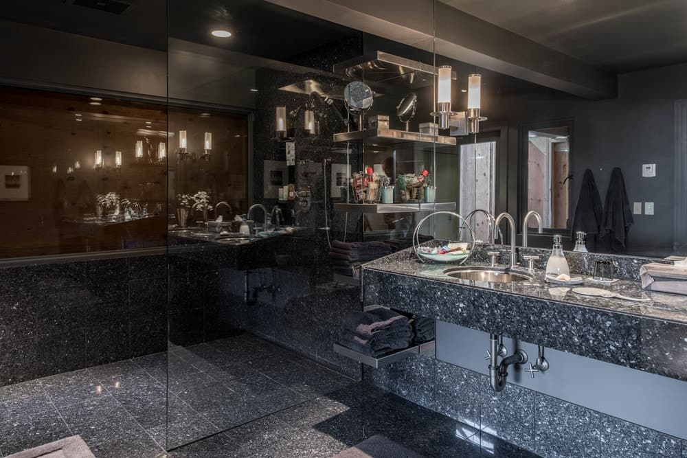 The bathroom has dark marble floating vanity that houses the sink topped with a large mirror that has attached wall lamps. Images courtesy of Toptenrealestatedeals.com.