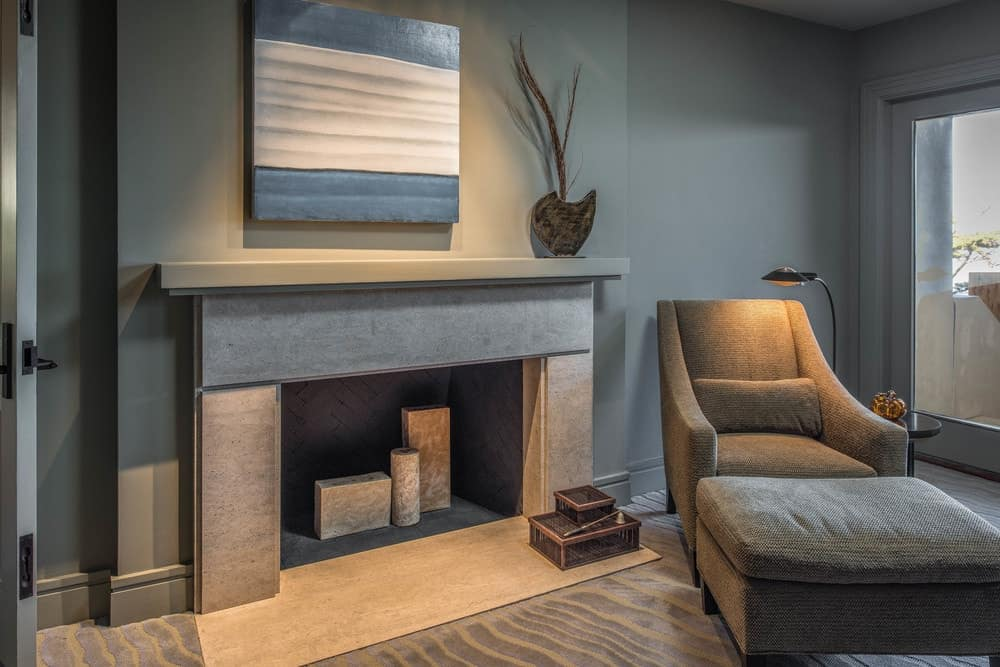 Across from the bed is a large concrete fireplace with a charming arm chair beside it that has its own foot stool for a comfortable reading nook. Images courtesy of Toptenrealestatedeals.com.