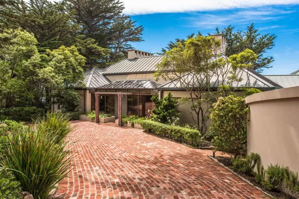 This is the front of the house with a charming red brick walkway leading to the main entry. This walkway is flanked by lush landscaping filled with shrubs and tall trees. Images courtesy of Toptenrealestatedeals.com.