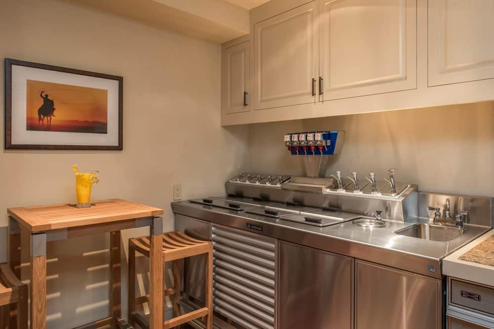 This is the second smaller kitchen with a simple stainless steel counter paired with a wooden tall table for a homey breakfast bar on the side. Images courtesy of Toptenrealestatedeals.com.