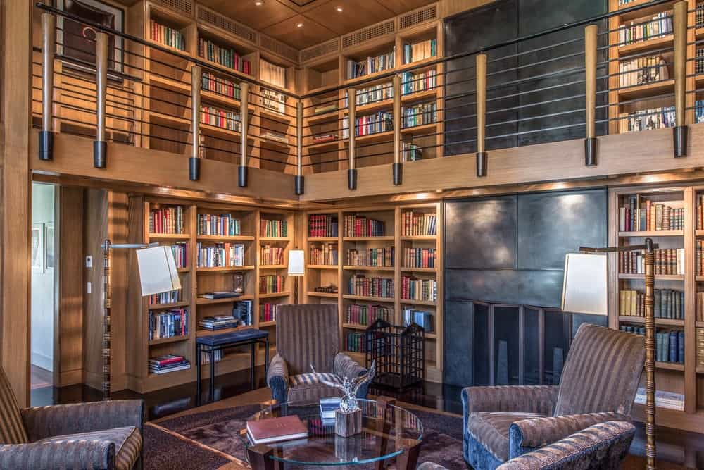 The gorgeous and unique library has two levels filled with wooden structures built into the walls filled with shelves and books. Images courtesy of Toptenrealestatedeals.com.