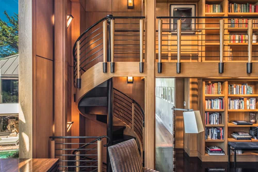 From the first level of the library, you can access the second level through a charming spiral staircase with wrought iron railings. Images courtesy of Toptenrealestatedeals.com.