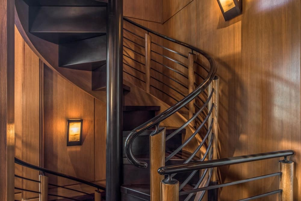 This is a closer look at the spiral staircase of the library made of black steel and wooden steps complemented by wall-mounted lamps on the wooden walls. Images courtesy of Toptenrealestatedeals.com.