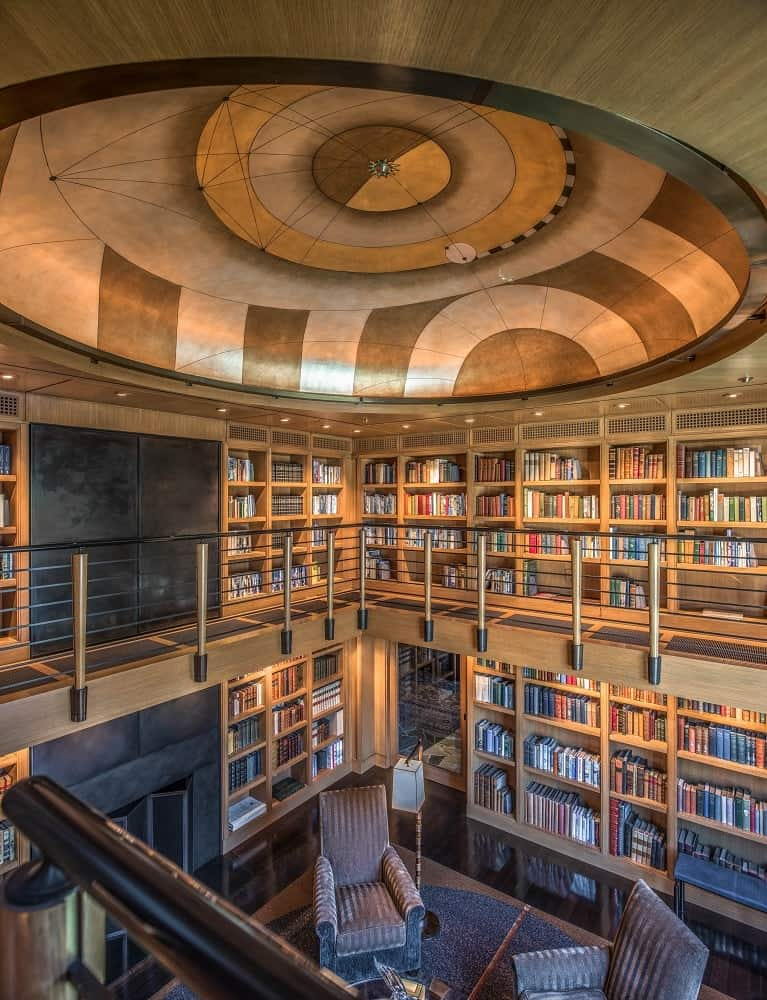This angle of the library as seen from the vantage of the second level shows the gorgeous wooden bookshelves of the walls filled with hundreds of books topped with a large cove ceiling with a unique design. Images courtesy of Toptenrealestatedeals.com.