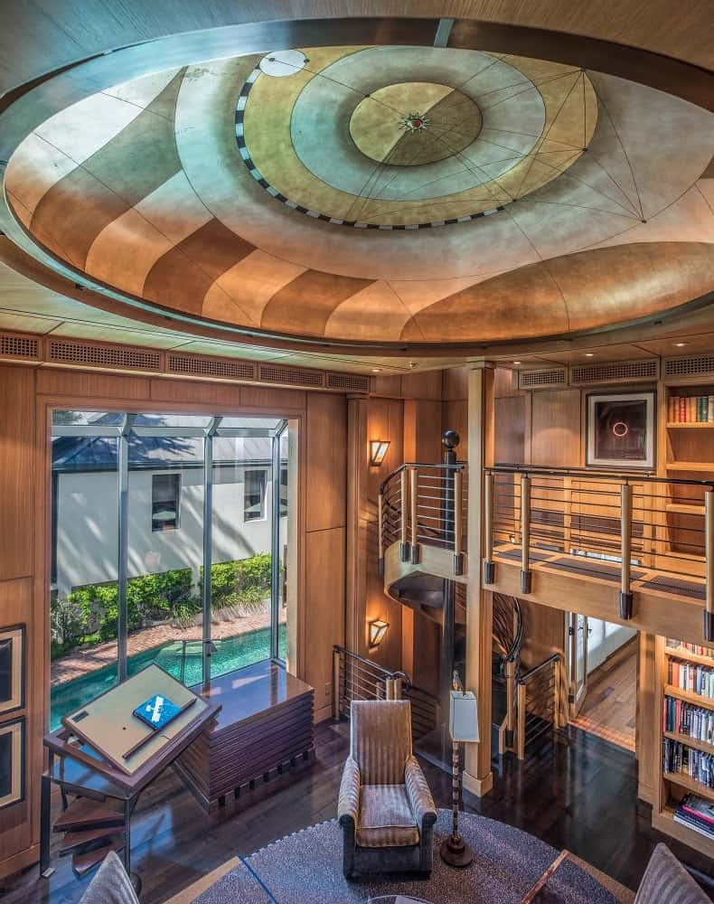 This is a full view of the library that has two levels with the second level forming an indoor balcony with wrought iron railings. Images courtesy of Toptenrealestatedeals.com.