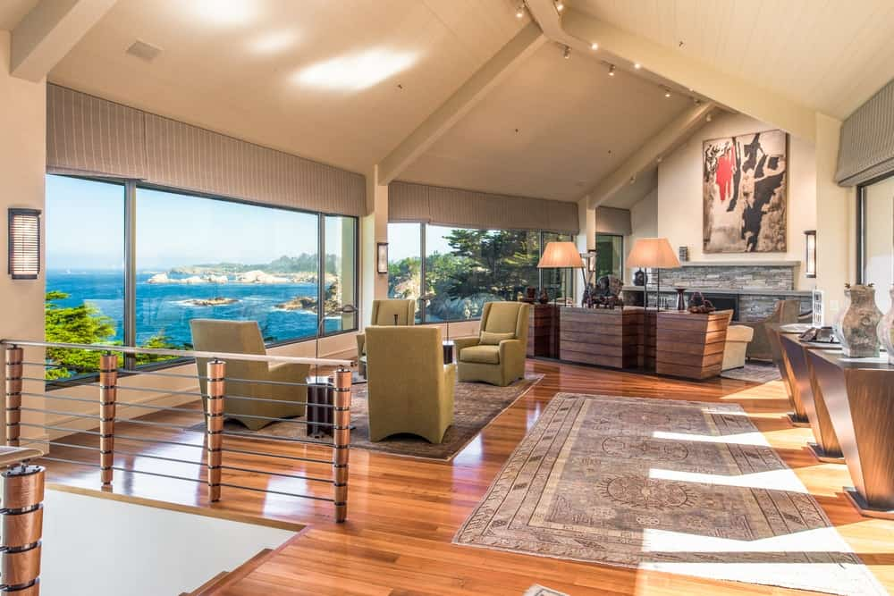 This is a bright and spacious great room that houses the living room on the far side and a sitting room beside it. These are complemented by a tall cathedral ceiling brightened by the glass walls. Images courtesy of Toptenrealestatedeals.com.