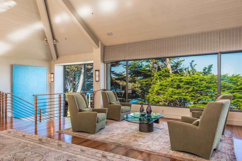 This is a closer look at the sitting area behind the living room with four green cushioned arm chairs facing a glass-top coffee table with a nice background of the scenic landscape view of the glass wall. Images courtesy of Toptenrealestatedeals.com.