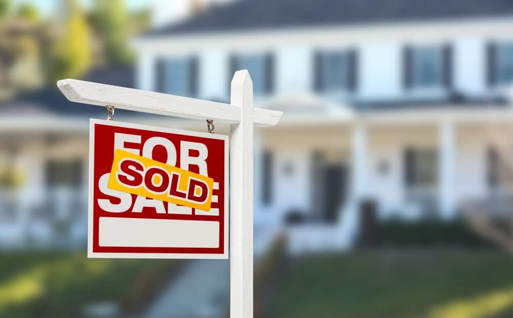 SOLD home signage with a blurred background of the house.