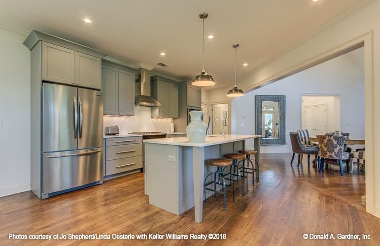 Kitchen with gray cabinets, stainless steel appliances, and a breakfast bar lined with round metal stools.