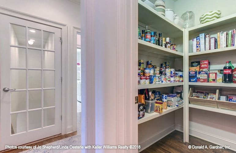 The walk-in pantry offers lots of storage filled with drinks and foods.