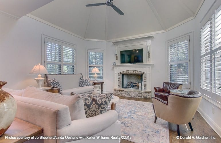 The hearth room has a high dome ceiling and louvered windows that bring natural light in.