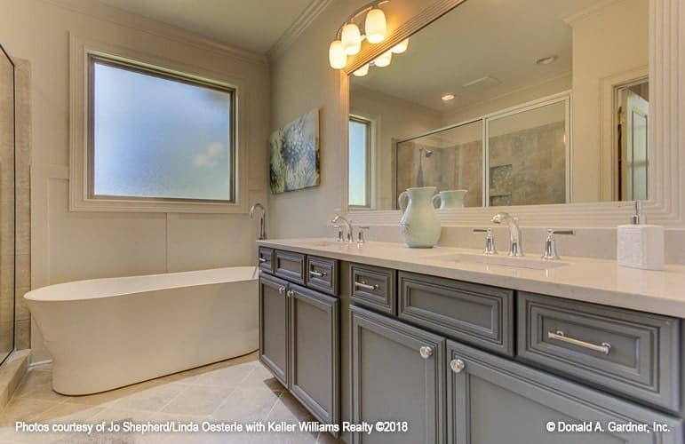 The primary bathroom is equipped with a freestanding tub and a dual sink vanity lit by warm sconces.