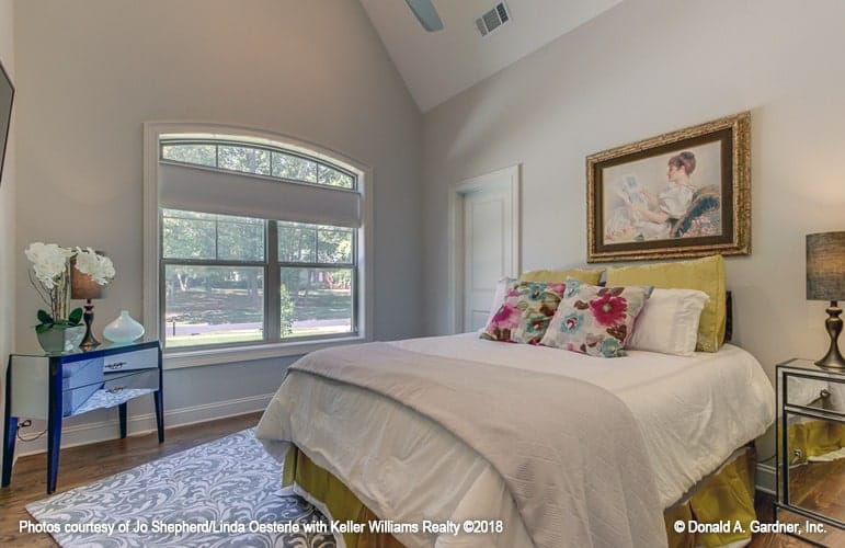 This bedroom has a cathedral ceiling and light gray walls adorned by a brass framed painting.