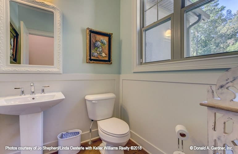 Kids' bathroom with a toilet and a pedestal sink paired with an ornate white mirror.