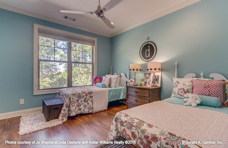 Girls' bedroom with beautiful blue walls and two comfy beds flanking the wooden dresser.