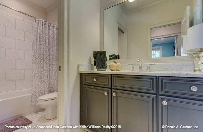 This bathroom offers a sink vanity, a toilet, and a tub and shower combo enclosed in a patterned curtain.