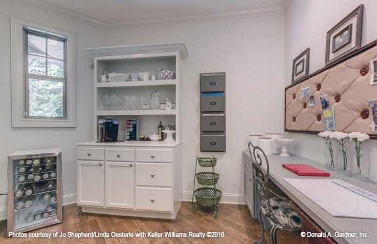 The study is filled with a white cabinet, beverage fridge and a long desk complemented with an ornate chair and tufted wall board.