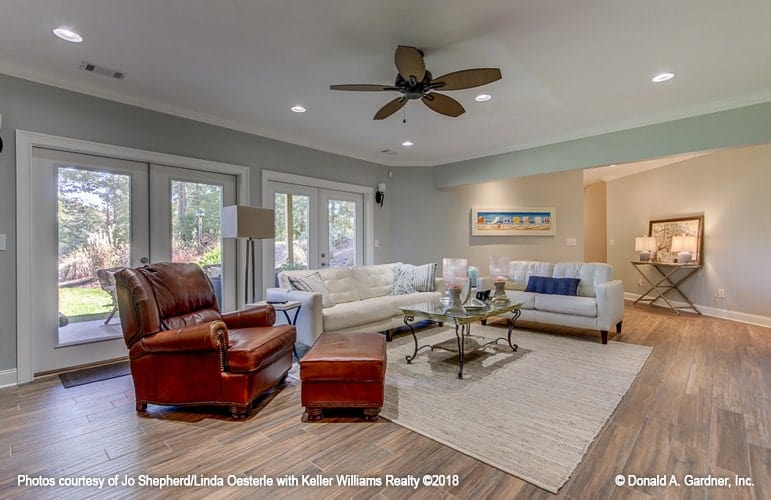 Family room with a brown leather lounge chair and white tufted sofas paired with a metal coffee table.