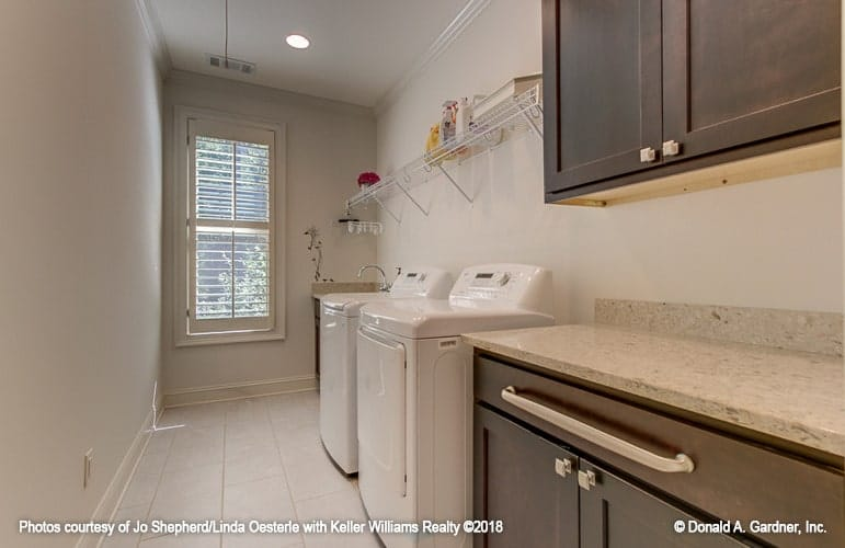Utility room with dark wood cabinets, granite countertops and top load washing machine and dryer under the white metal rack.
