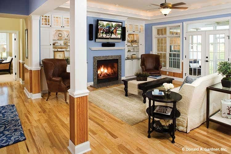 The living room has a fireplace, brown wingback chairs, and a skirted sofa surrounding the black coffee table.