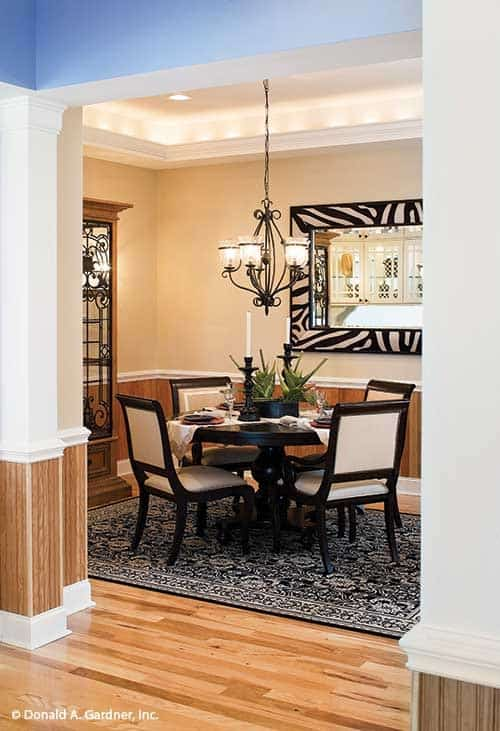 Formal dining room with a glowing tray ceiling and beige walls adorned by a zebra framed mirror and wooden wainscoting.