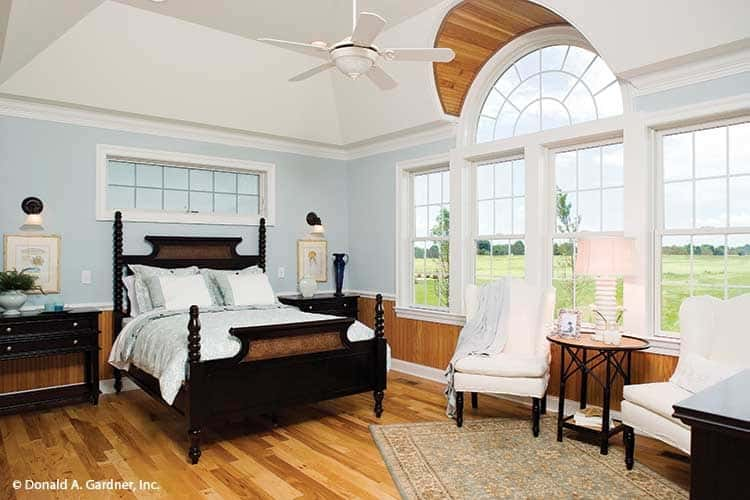 The primary bedroom is filled with dark wood furniture and a sitting area by the white framed windows bringing plenty of natural light in.