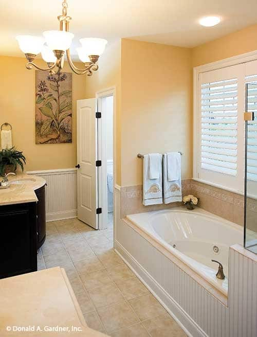 The primary bathroom offers two sink vanities, a separate shower, and a drop-in tub under the white louvered window.