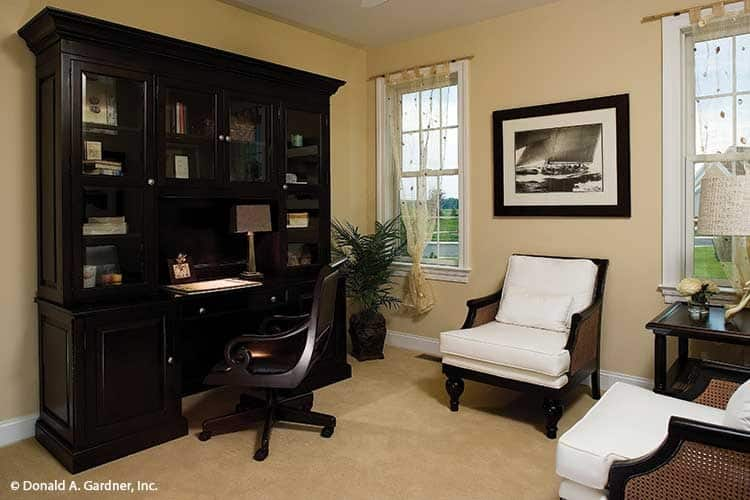Home office with a dark wood built-in, cozy seats, and beige walls that blend in with the carpet flooring.