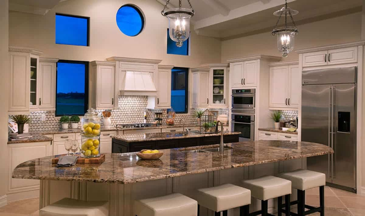 Home's kitchen with white cabinetry and two islands illuminated by a pair of glass pendants.