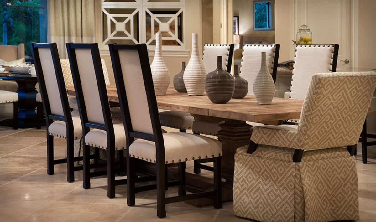 Dining room with upholstered chairs and a lengthy natural wood dining table topped by beautiful vases.