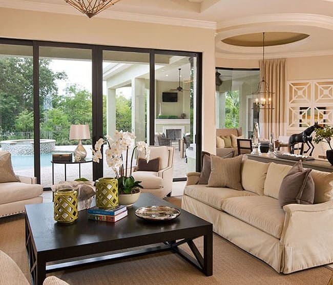 Living room with cozy beige seats and collapsible glazed doors that open out to the lanai.