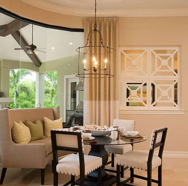 Dinette with a round glass top table paired with cushioned chairs and a beige wingback bench.