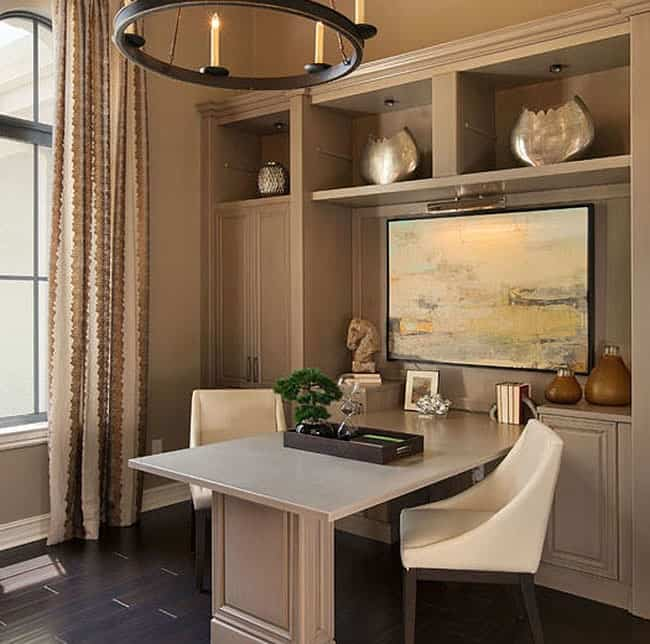 The home office offers built-in shelves and a light wooden desk flanked by modern upholstered chairs.
