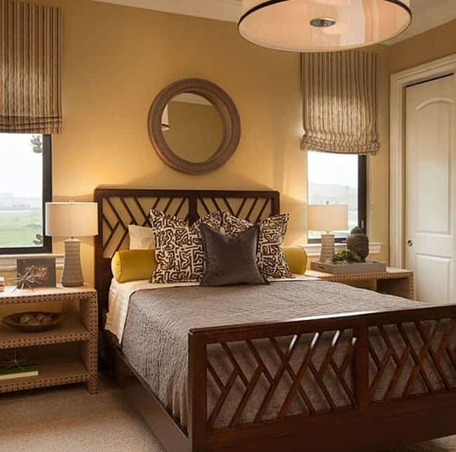 Another bedroom with a round mirror and wooden bed sandwiched by two nightstands.