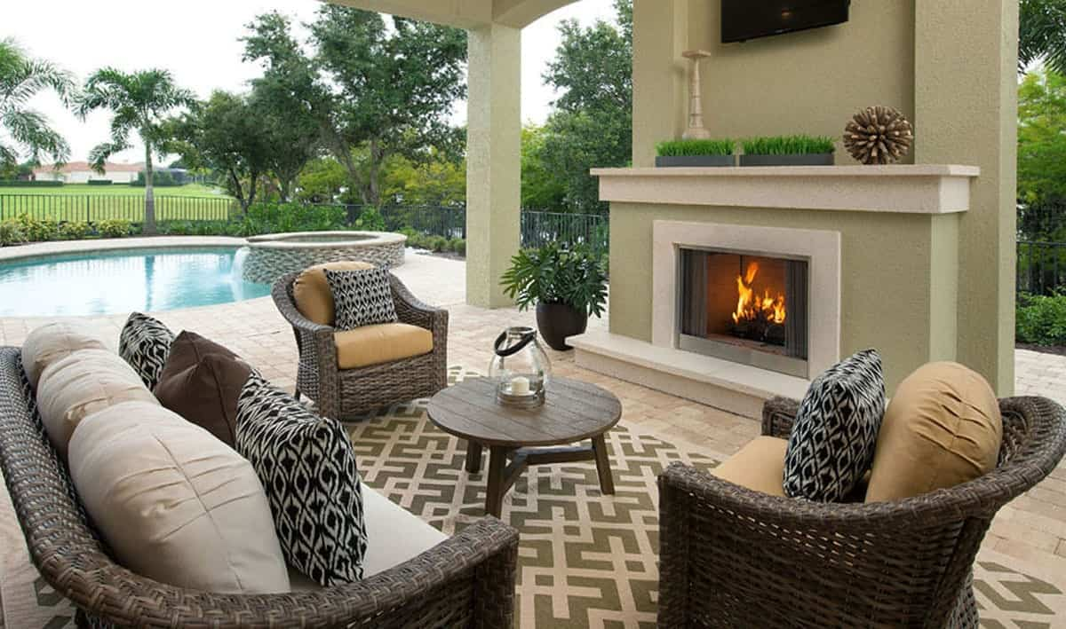 Outdoor living filled with a fireplace, wicker seats and a round center table over a green patterned rug.