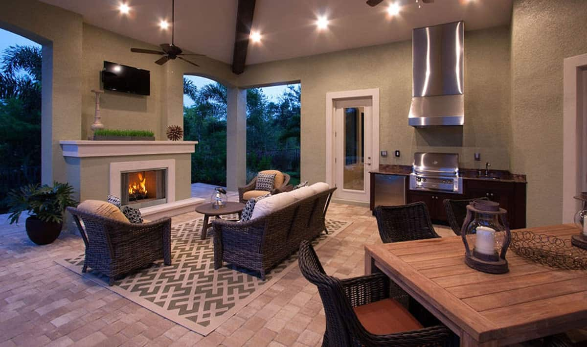 The outdoor kitchen behind the outdoor living offering stainless steel appliances and a wicker dining set.