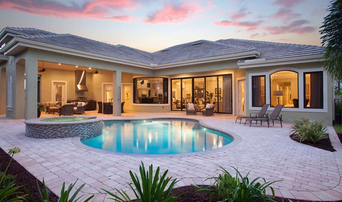 Rear view of the house shows the covered lanai and a freeform pool integrated with a spa.