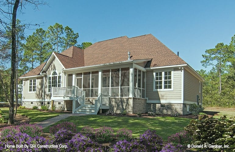 Home's rear exterior view shows the beige siding, stone bricks base, and a screened porch framed with white railings and columns.